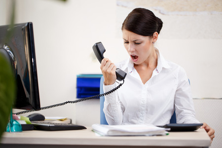 Angry woman on the phone on hold with a business